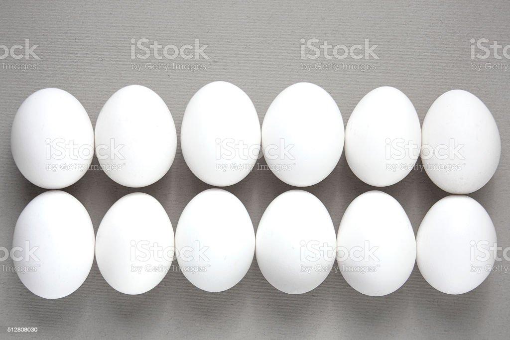Dozen white eggs on a gray background. stock photo
