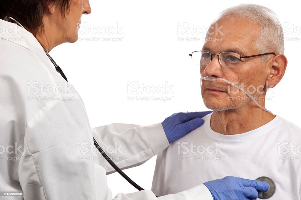 Dr checking heart with stethoscope on patient with breathing tube stock photo