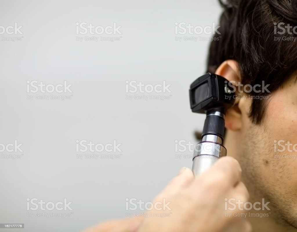 Dr. Examining Patient's Ear with an Otoscope stock photo
