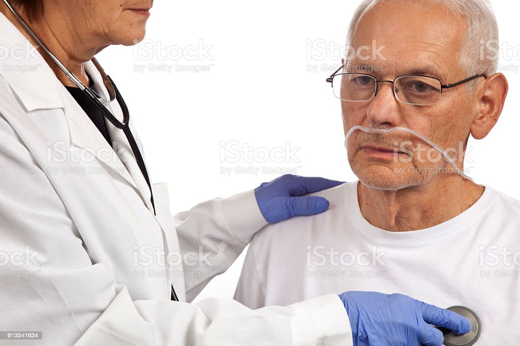 Dr. with stethoscope examining patient with oxygen tubes in nostrils stock photo