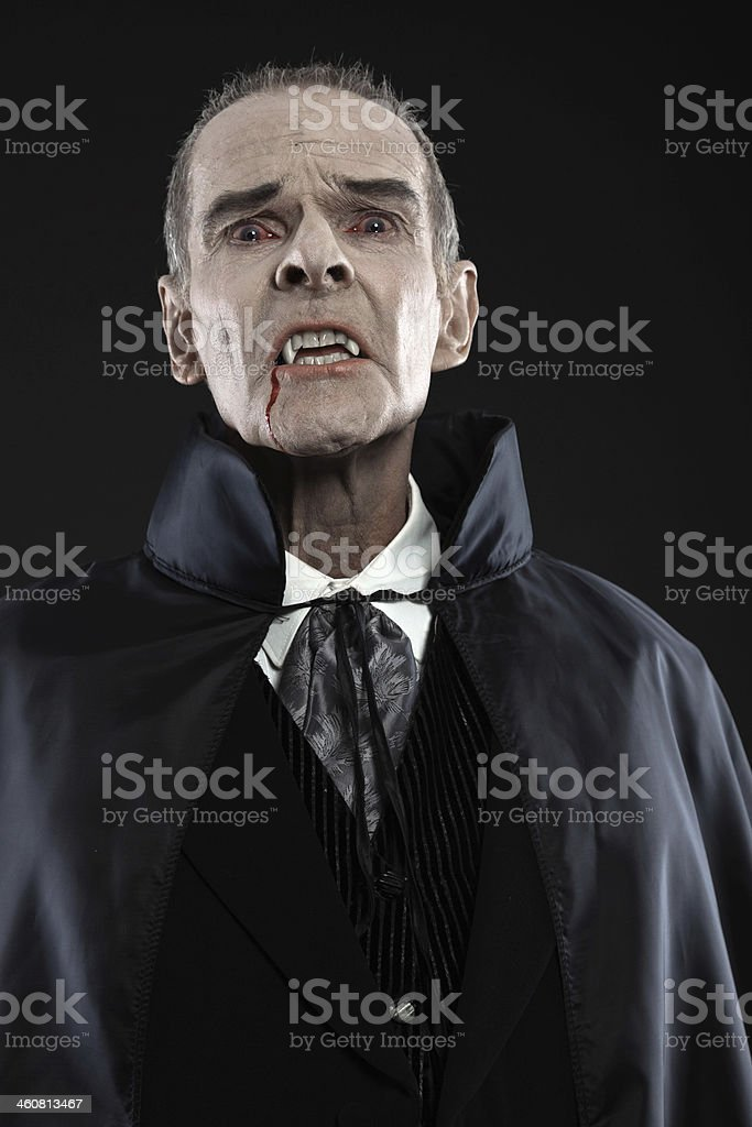 Dracula with black cape showing his scary teeth. Vamp fangs. royalty-free stock photo