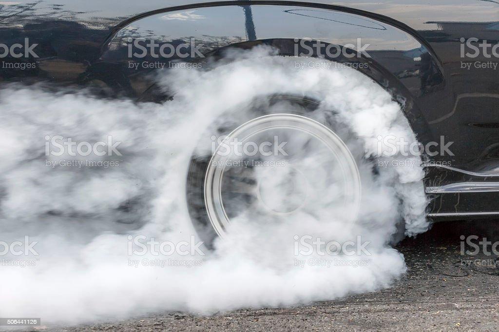 Drag racing car burns rubber off its tires stock photo