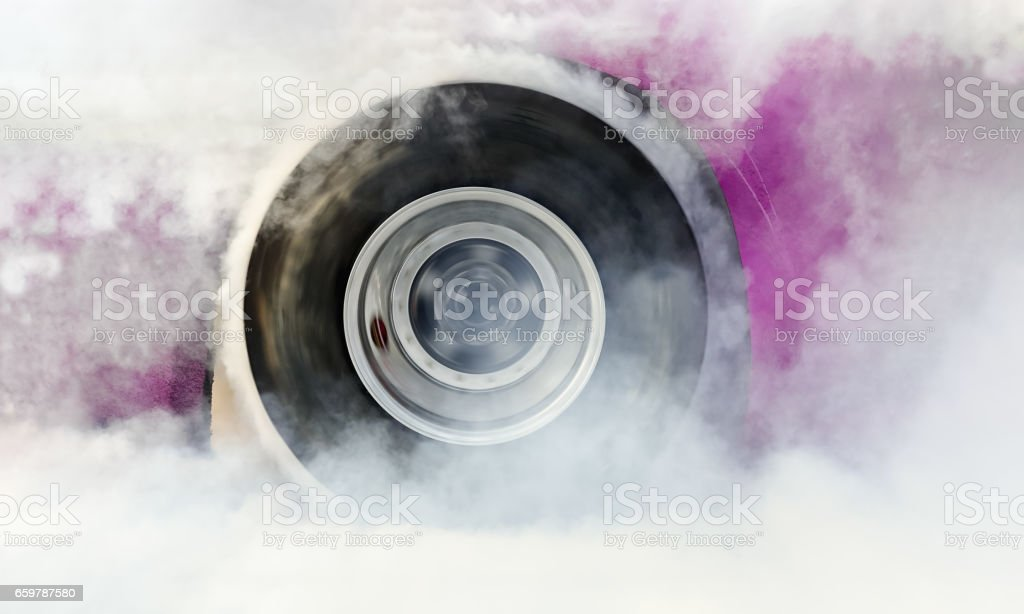 Drag racing car burns rubber off tire for the race stock photo