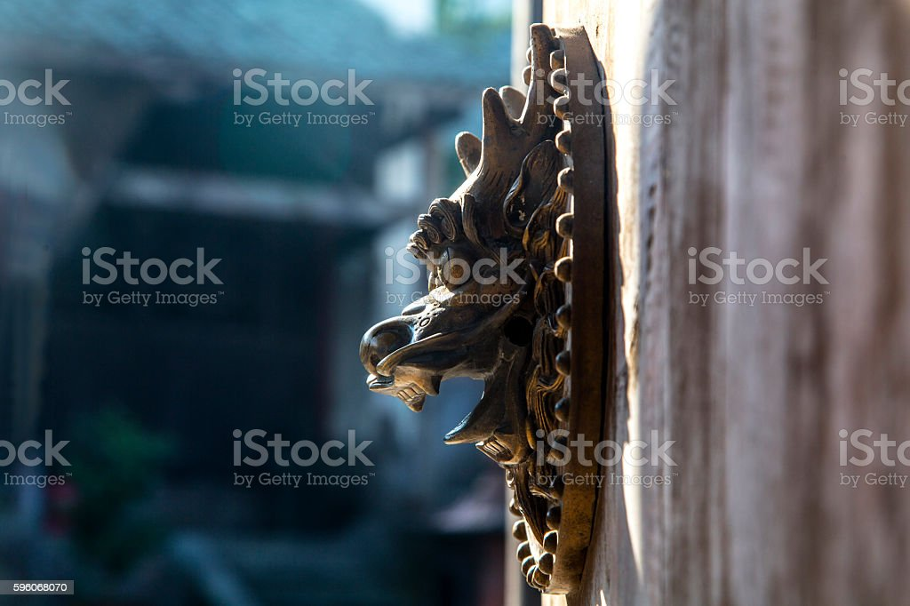 dragon door knocker on wooden gate stock photo