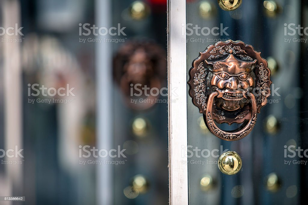 dragon knocker on glass door of a shop stock photo