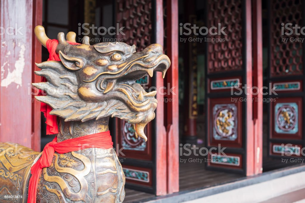 Dragon statue with a red stripe at the entry of a temple in China stock photo