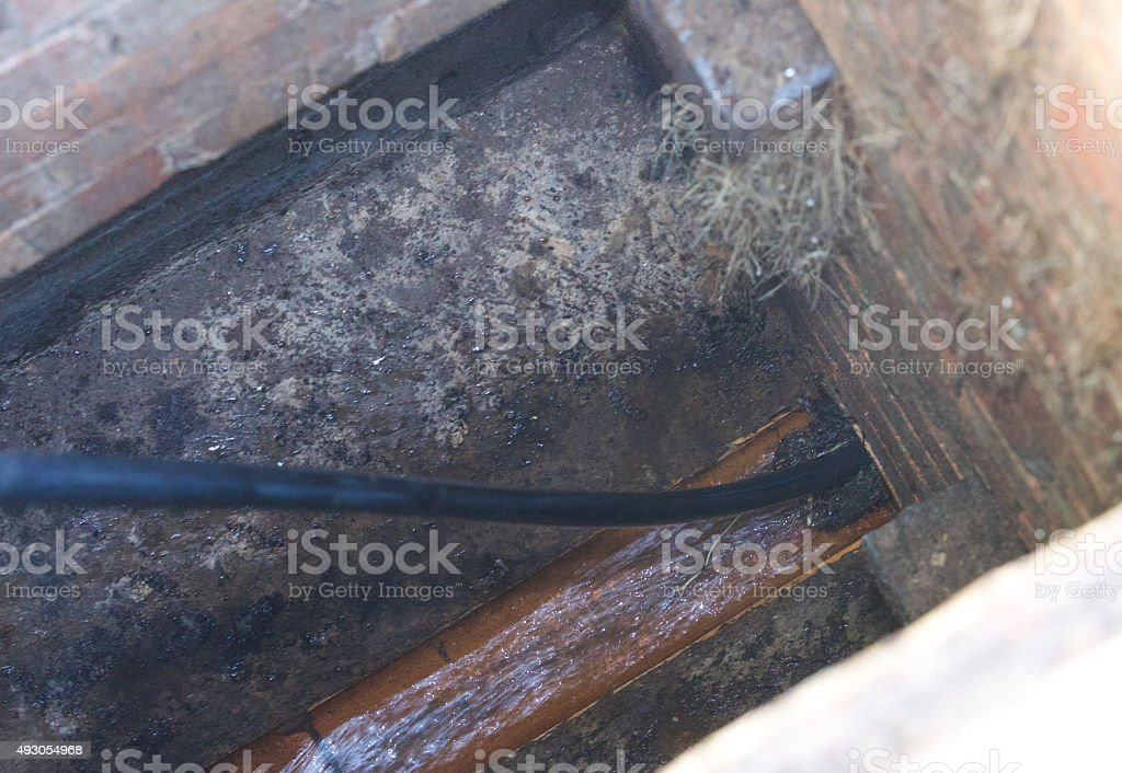 Drain being jetted clean - tree roots are stopping flow stock photo