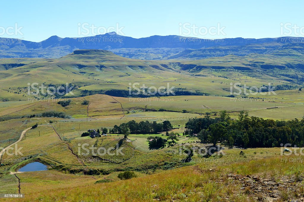 Drakensberg mountains with grass and trails and blue sky stock photo