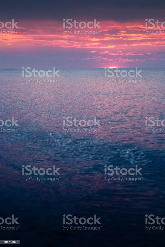 Dramatic and colorful sunset with clouds at North sea coast stock photo