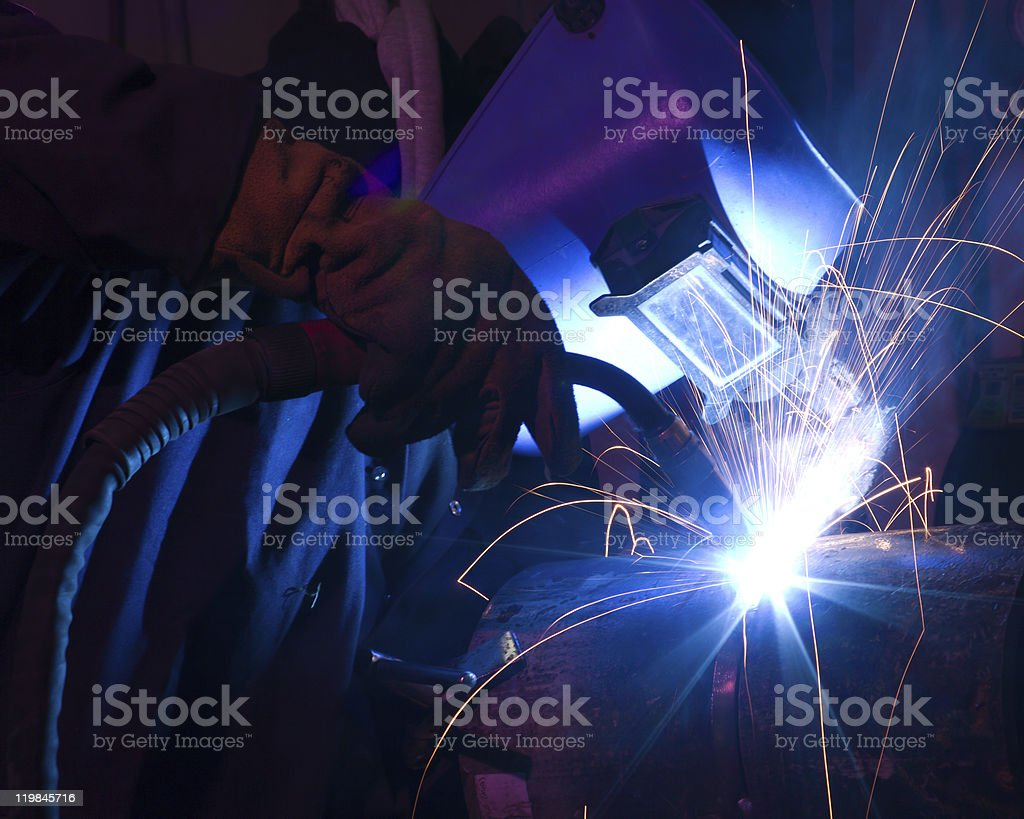 Dramatic blue-lit MIG welding close stock photo