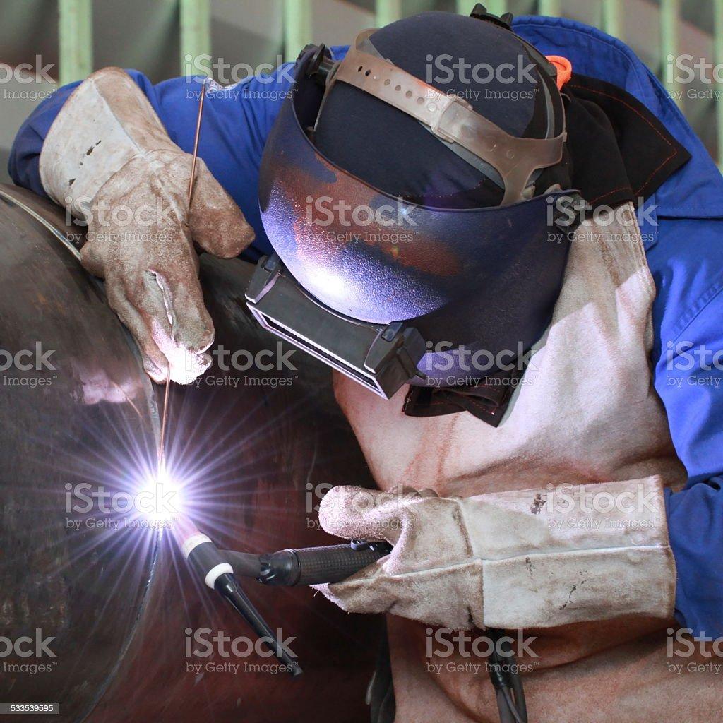 Dramatic blue-lit MIG welding close stock photo