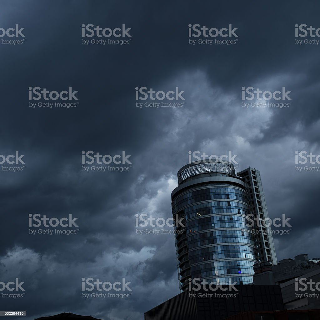 Dramatic building at dark cloudy overcast sky stock photo