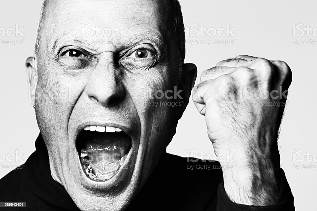 Dramatic close-up portrait of furious, aggressive man yelling, shaking fist stock photo