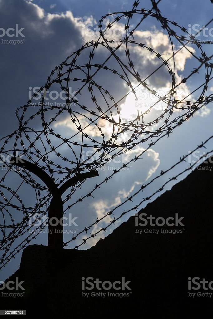 Dramatic clouds behind barbed wire fence on a prison wall stock photo
