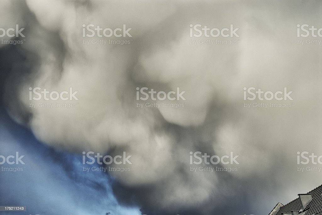 Dramatic clouds over rooftop royalty-free stock photo