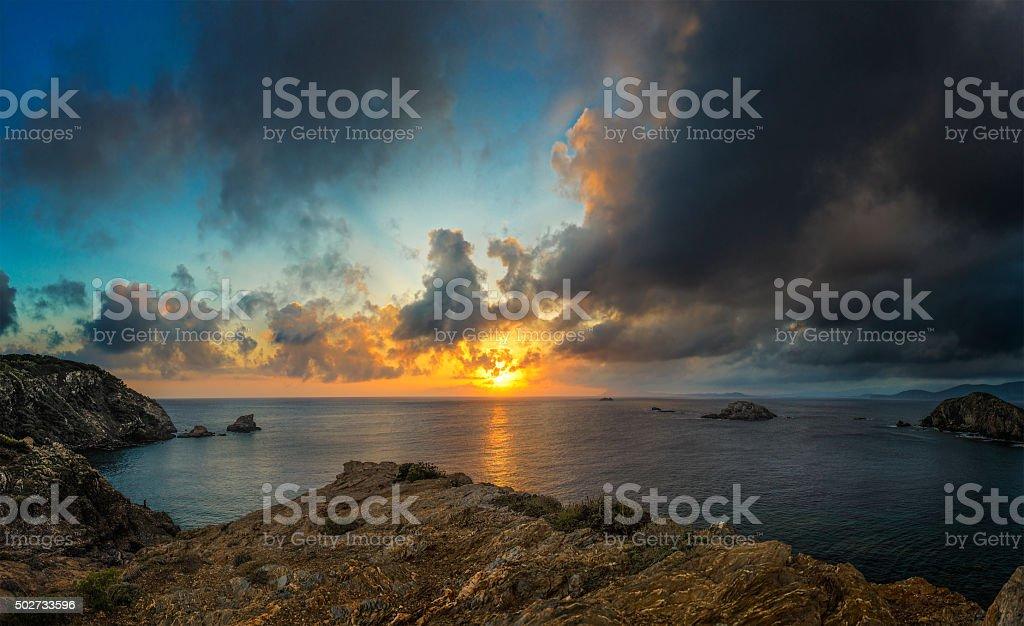 Dramatic cloudscape over rocky coastline - panorama stock photo