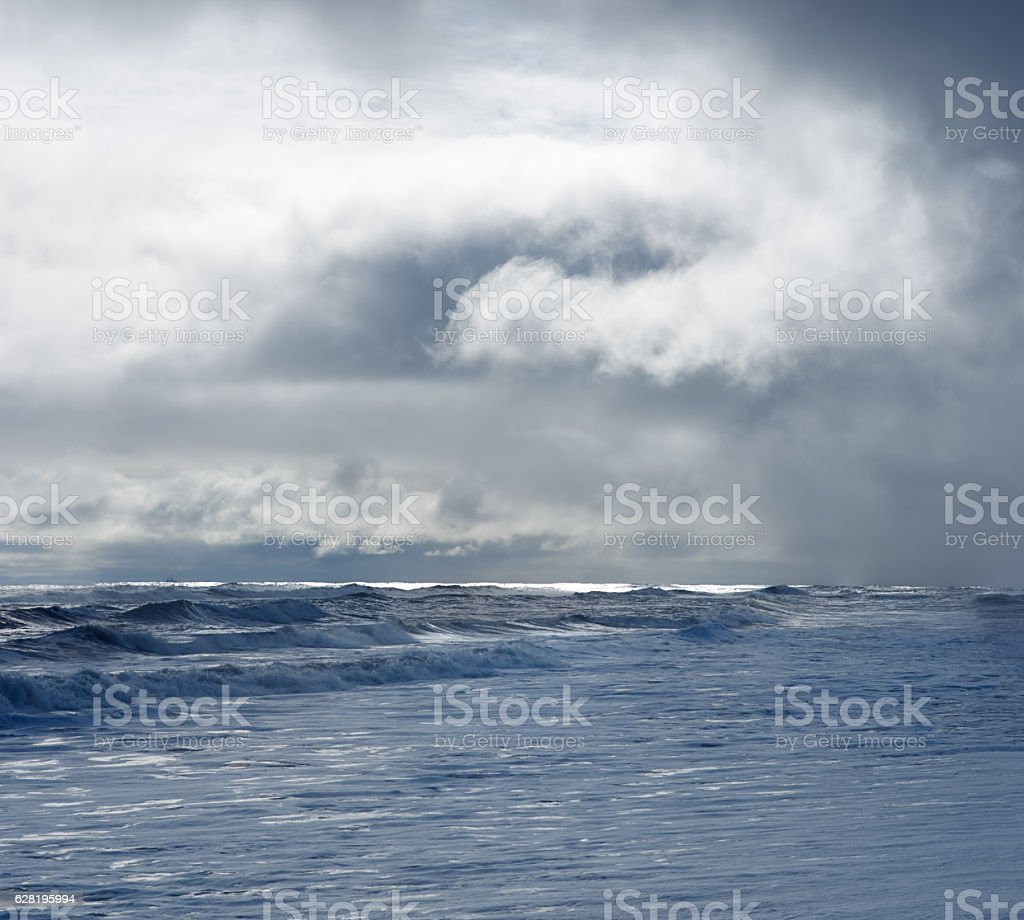 Dramatic cloudy sky over dark water ripple surface sea, sunlight stock photo