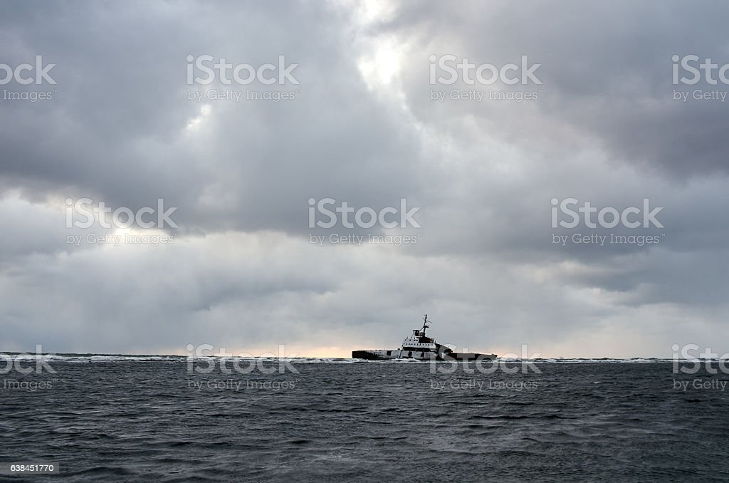 Dramatic cloudy sky over sea, old shipwreck ruins stock photo