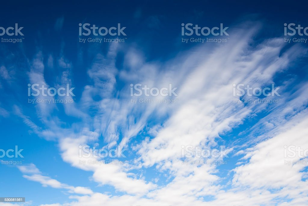 dramatic deep blue sky with streaky clouds stock photo