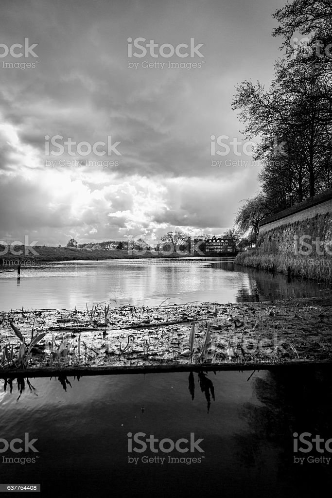 Dramatic Dutch landscape with canal , dike, and threatening clouds stock photo
