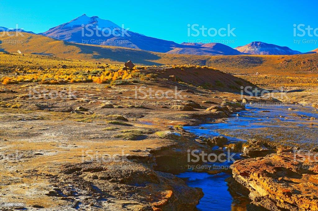 Dramatic Landscape: Tatio Geysers river stream at sunrise and Idyllic Atacama Desert steppe, snowcapped Volcanic landscape panorama – San Pedro de Atacama, Chile, Bolívia and Argentina border stock photo