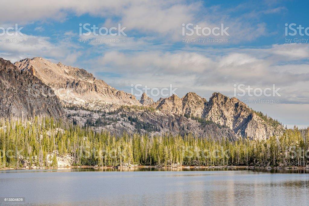 Dramatic lighting on jagged mountain peaks with lake stock photo