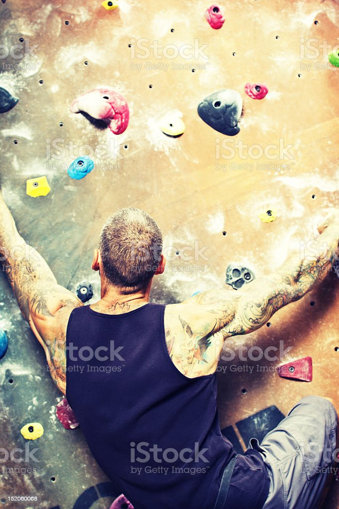 Dramatic Man Climbing Rock Wall stock photo