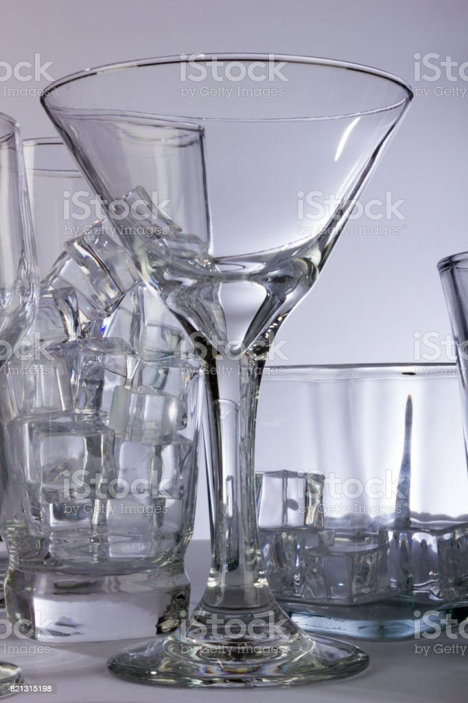 Dramatic Martini Glass with Many Other Glasses stock photo