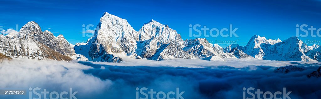 Dramatic mountain peaks panorama snowy summits above clouds Himalayas Nepal stock photo
