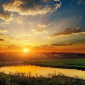 dramatic orange sunset over river