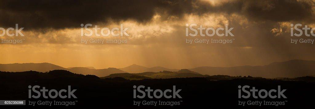 Dramatic panorama - sun beams bursting through dark stormy clouds stock photo