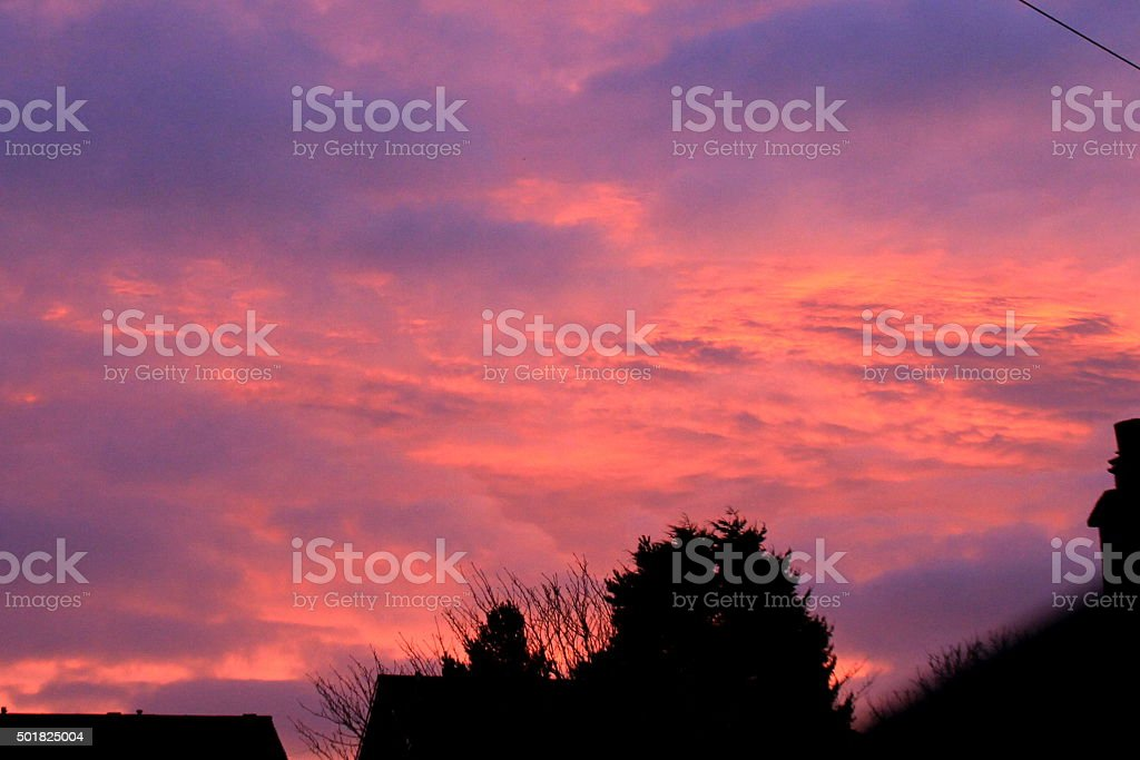 Dramatic Red sunrise on Pennines, West Yorkshire, rooftops trees silhouette stock photo