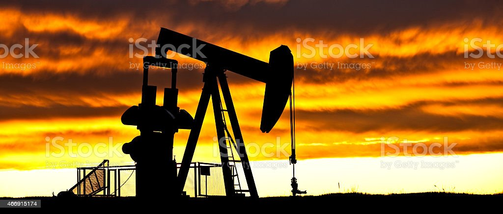 Dramatic Silhouette of Pumpjack in Alberta Oilfield stock photo