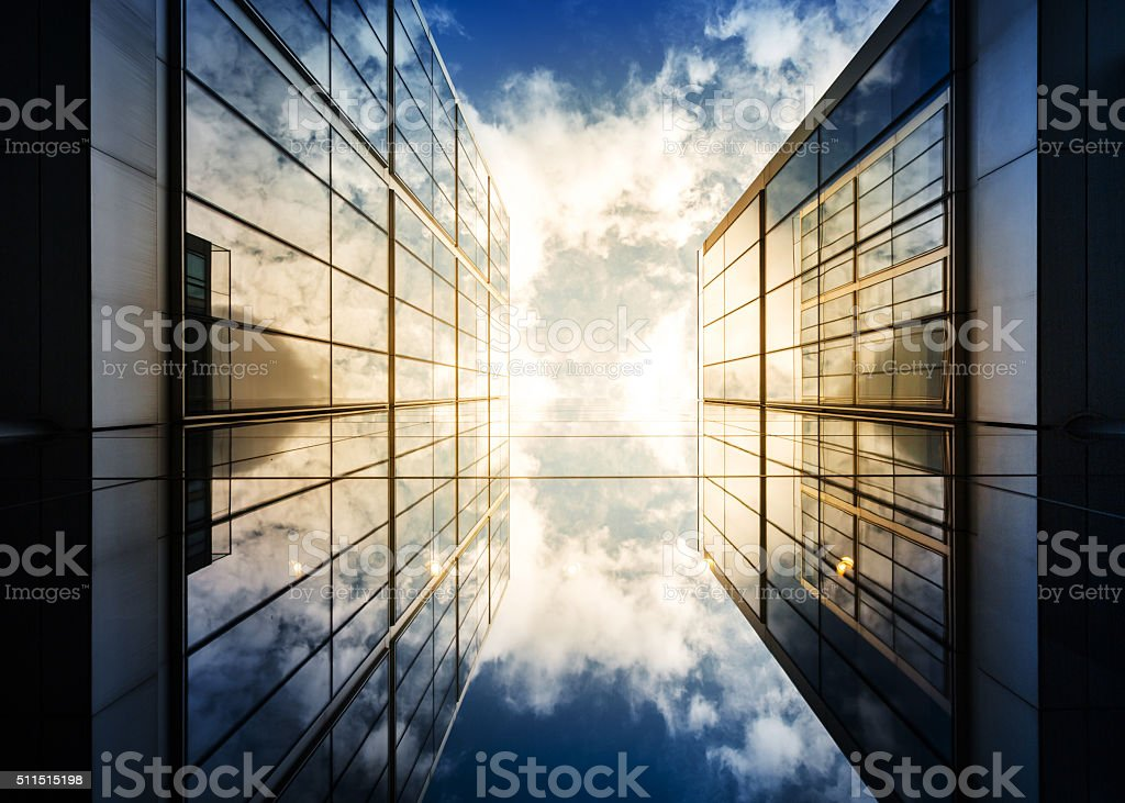 Dramatic sky and sun reflecting in corporate architecture.