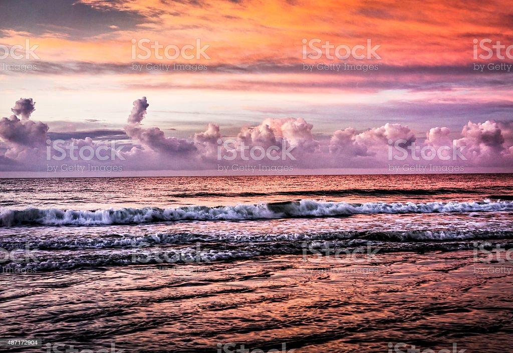Dramatic sky at sunrise or sunset along the beach stock photo