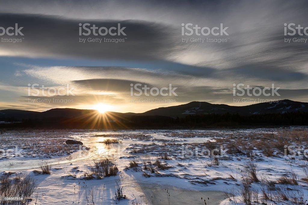 Dramatic Sky at Sunrise over Frozen Landscape stock photo