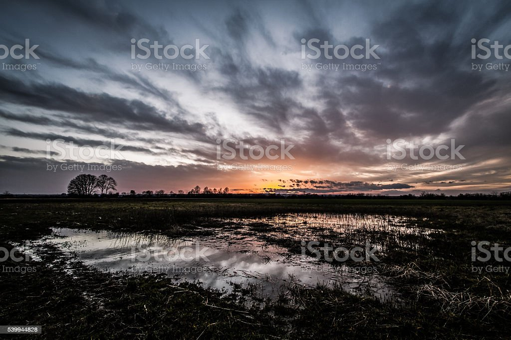 Dramatic sky over a puddle stock photo
