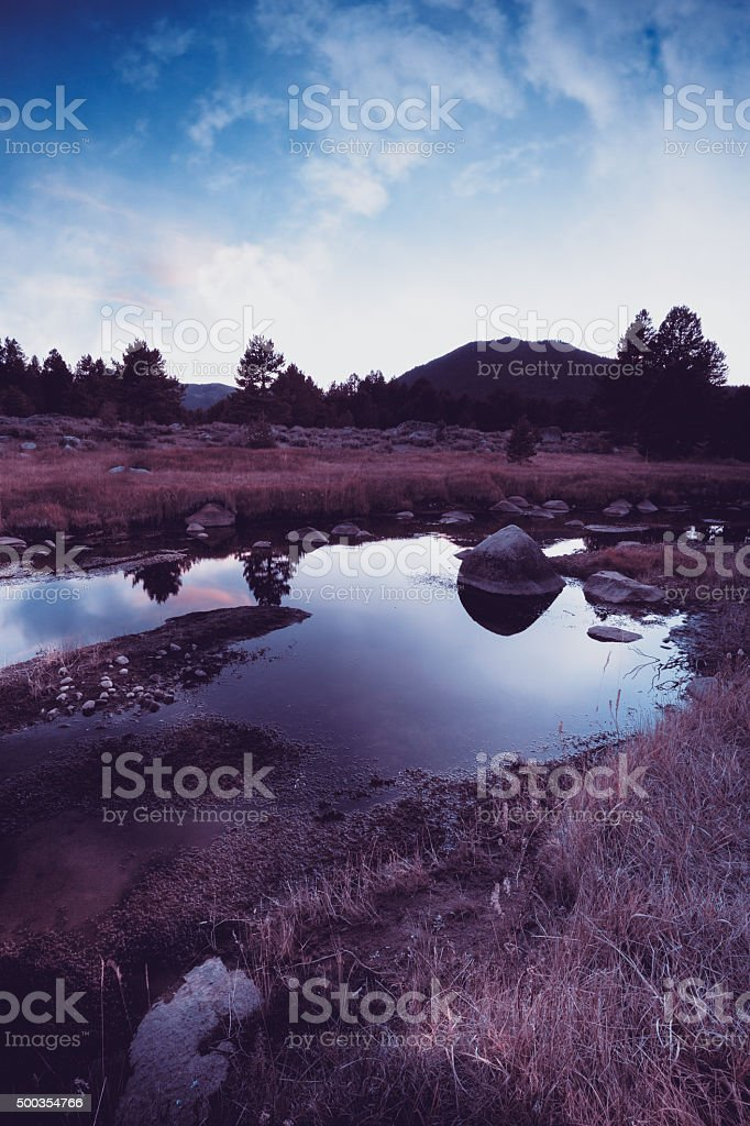 Dramatic sky over a small river  and silhouetted mountain stock photo