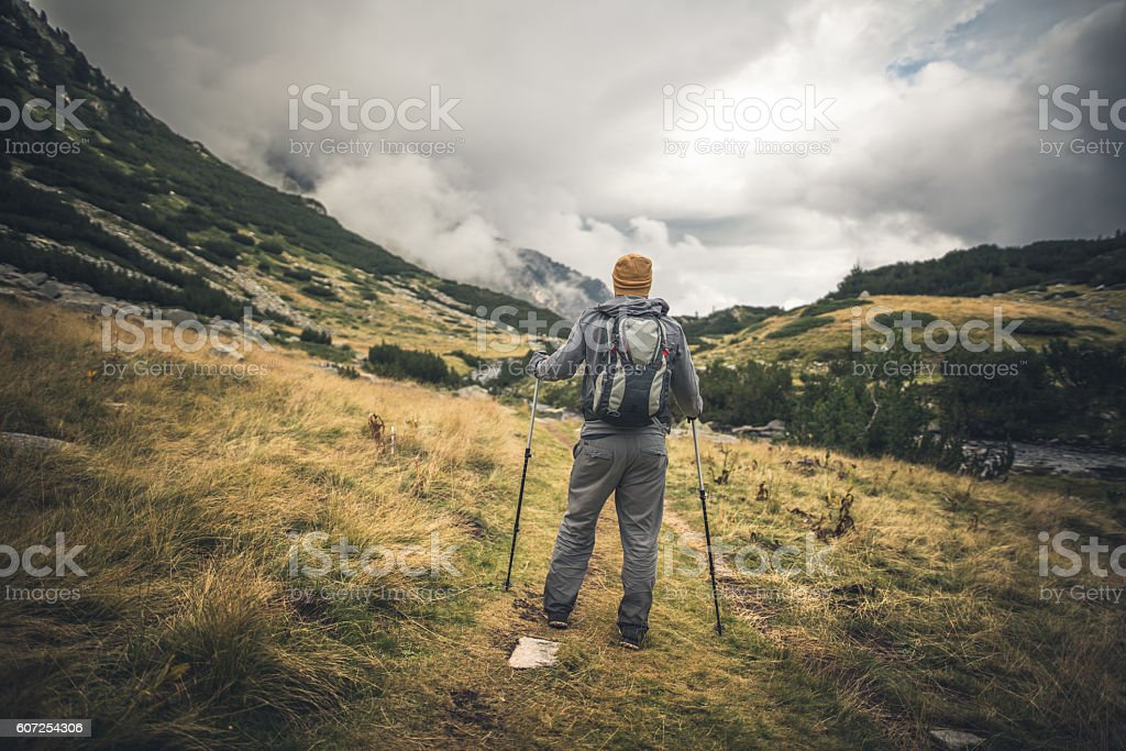 Dramatic sky over traveler walking alone in the mountains stock photo