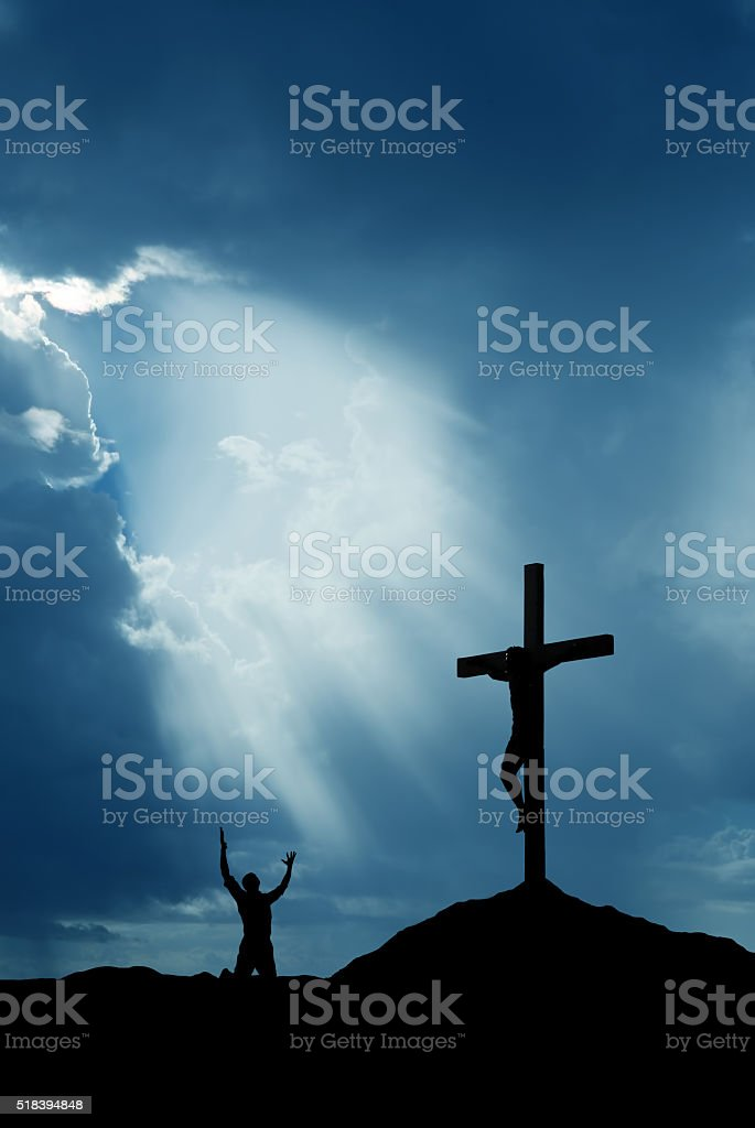 Dramatic sky scenery with cross and a worshiper vertical image stock photo