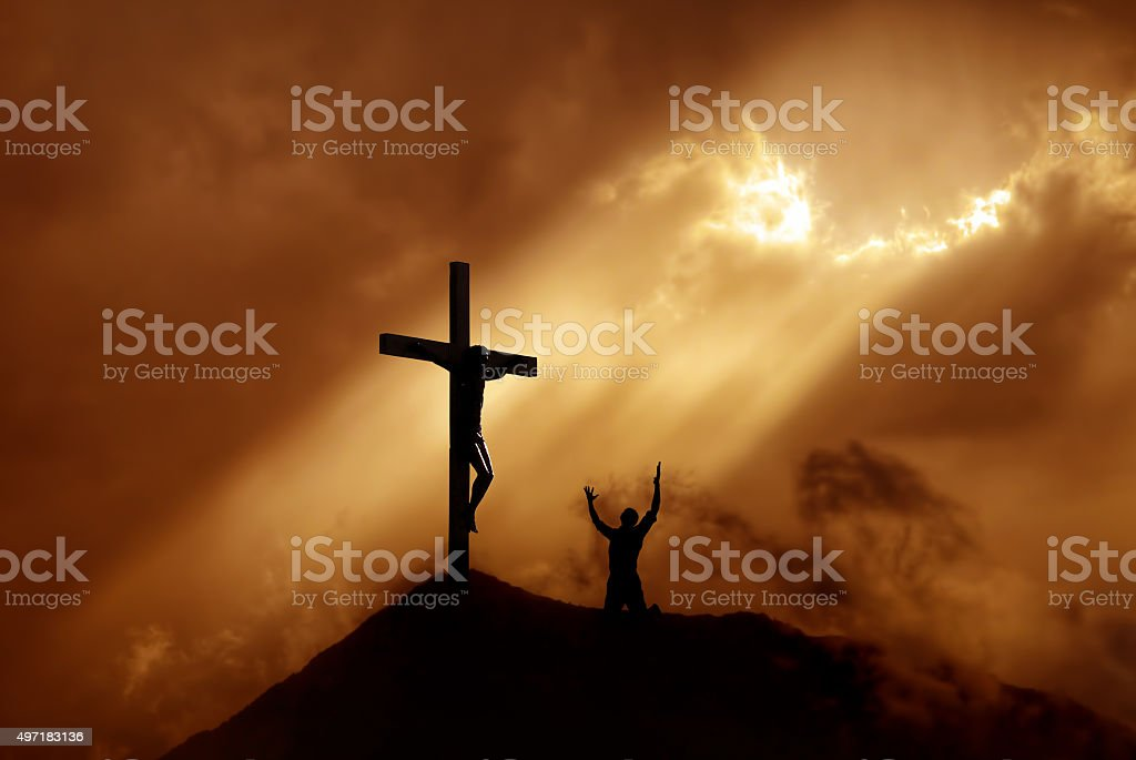Silhouette of a man praying before a cross at sunset concept of...