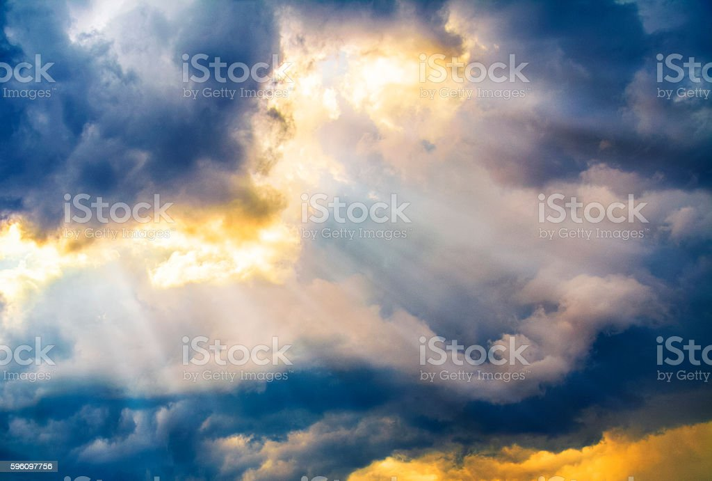 Dramatic sky with sun beams coming through the clouds stock photo