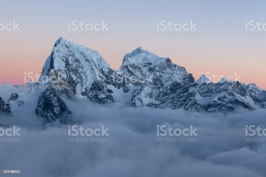 Dramatic snowy peak  of mount Cholatse rising above field of clouds. Picturesque mountain valley filled with curly clouds at sunset. Everest region, Sagarmatha National Park, Nepal, Himalayas. stock photo