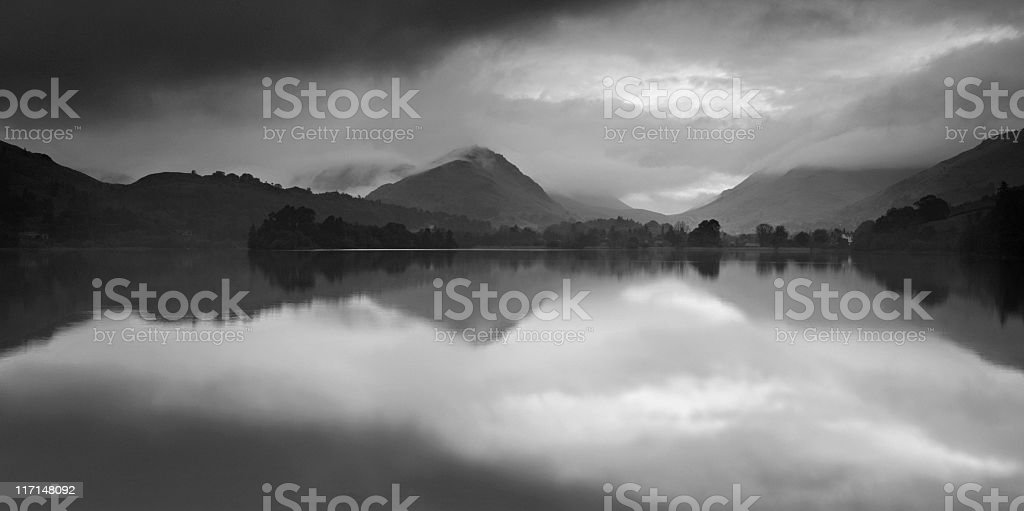 Dramatic Storm Clouds over Mountain Lake at Dawn stock photo