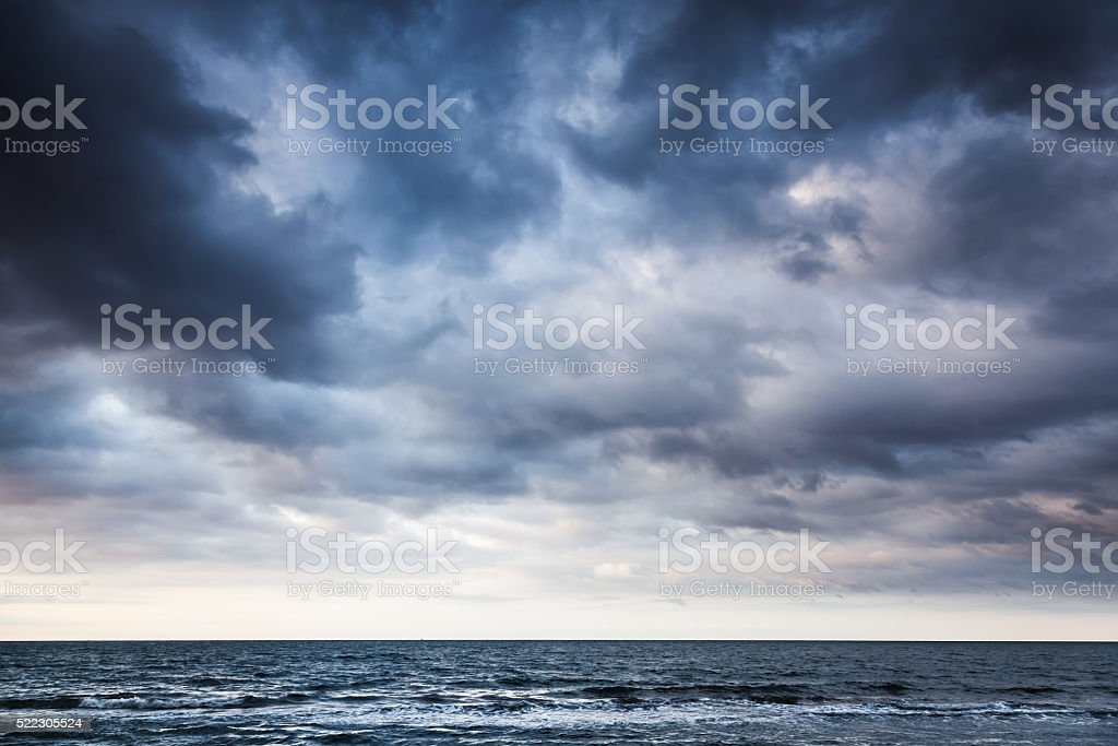 Dramatic stormy dark cloudy sky over sea stock photo