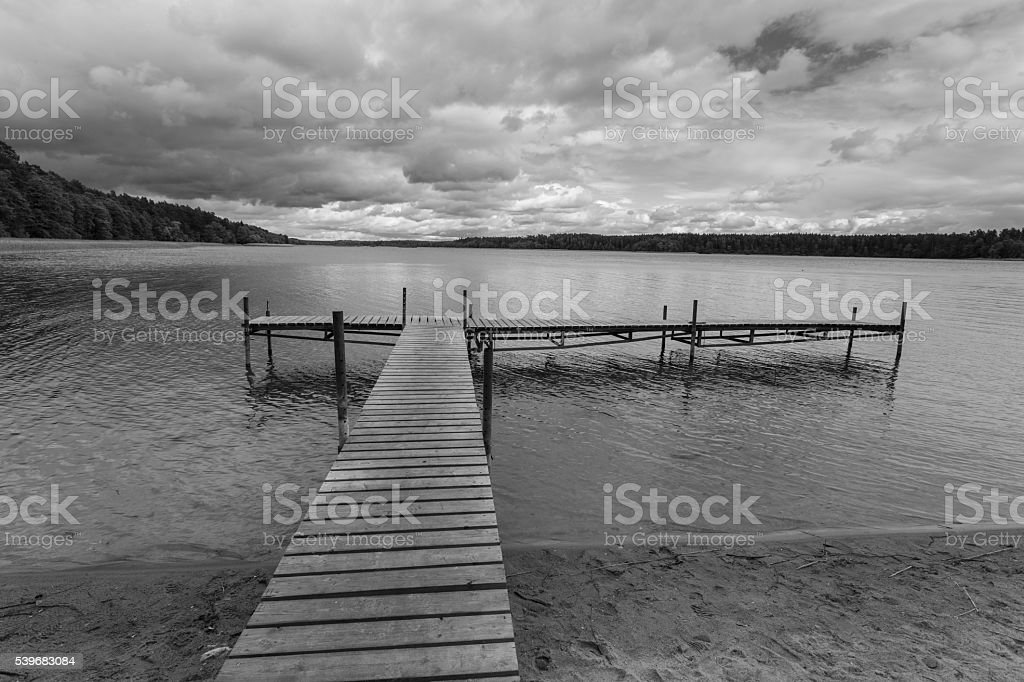 Dramatic stormy sky over lake and bridge stock photo