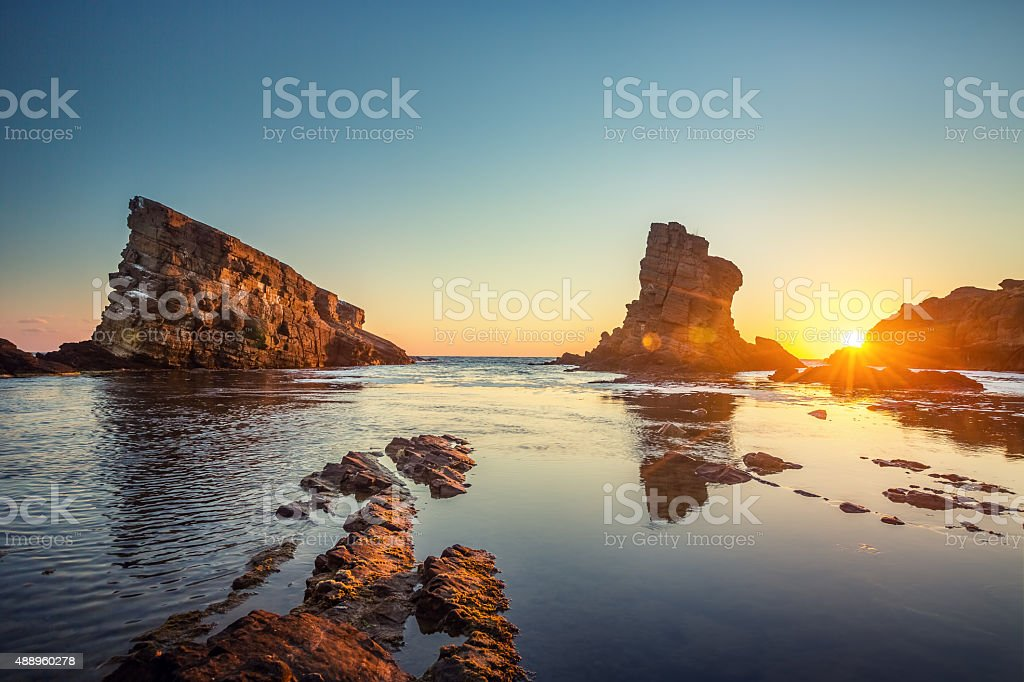 Dramatic sunrise with mist on the beach with rocks stock photo