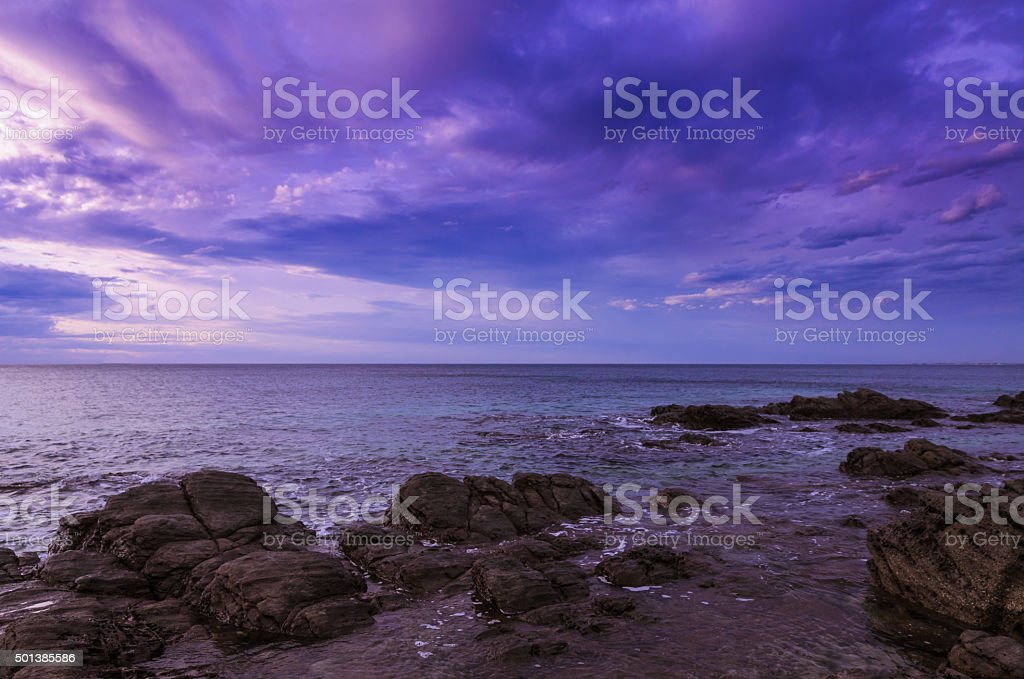 Dramatic sunset at the ocean with boulder rocks stock photo