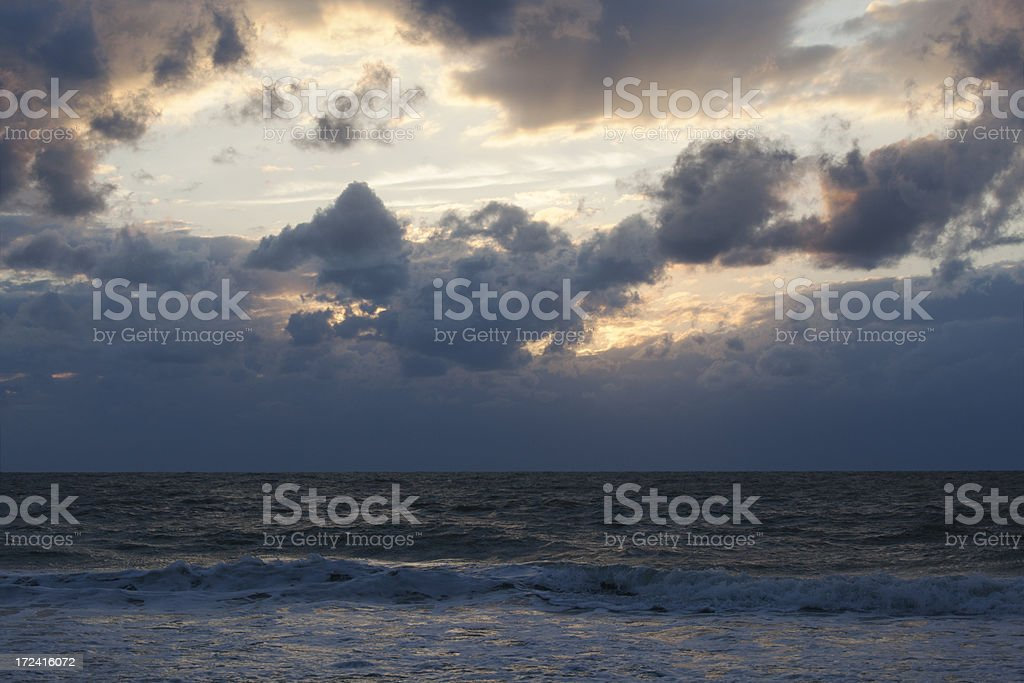Dramatic Sunset Clouds over Water Horizon stock photo