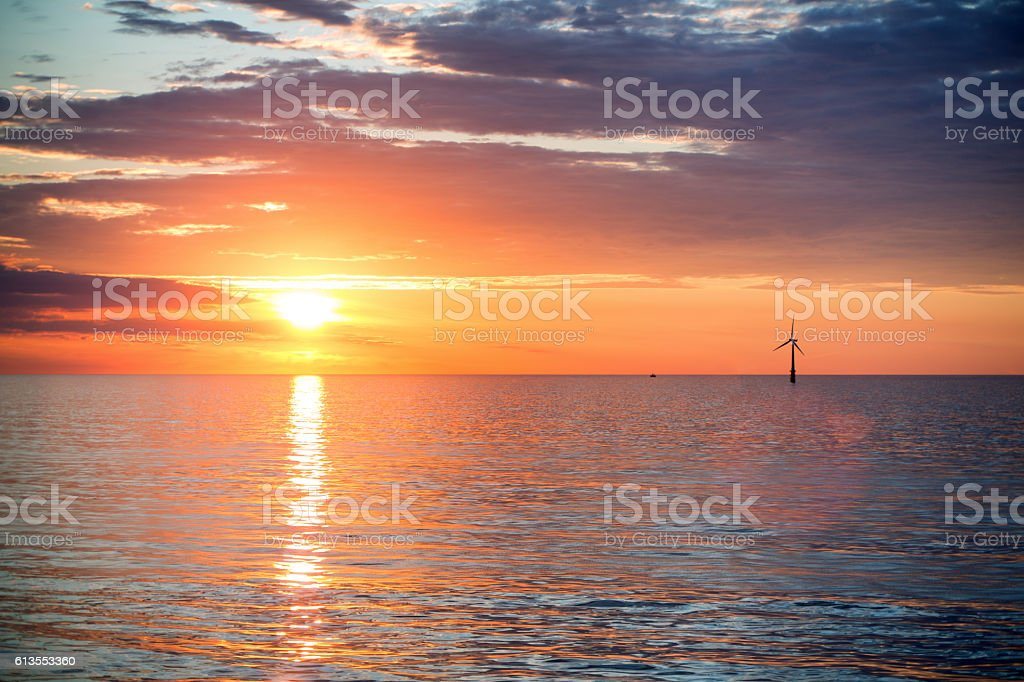 Dramatic Sunset or Sunrise over Ocean, Moody Sky Wind Turbine stock photo